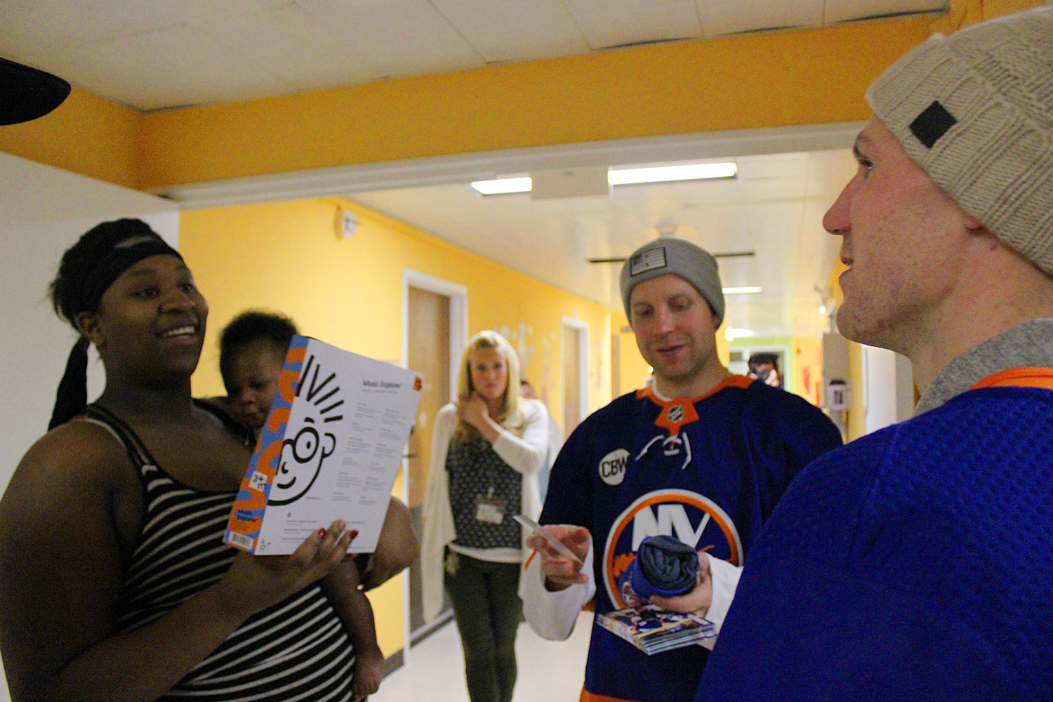Leo Komarov and Casey Cizikas gave a Christmas present to Tia Thomas, left, for her five-month-old son Ezra Michel.