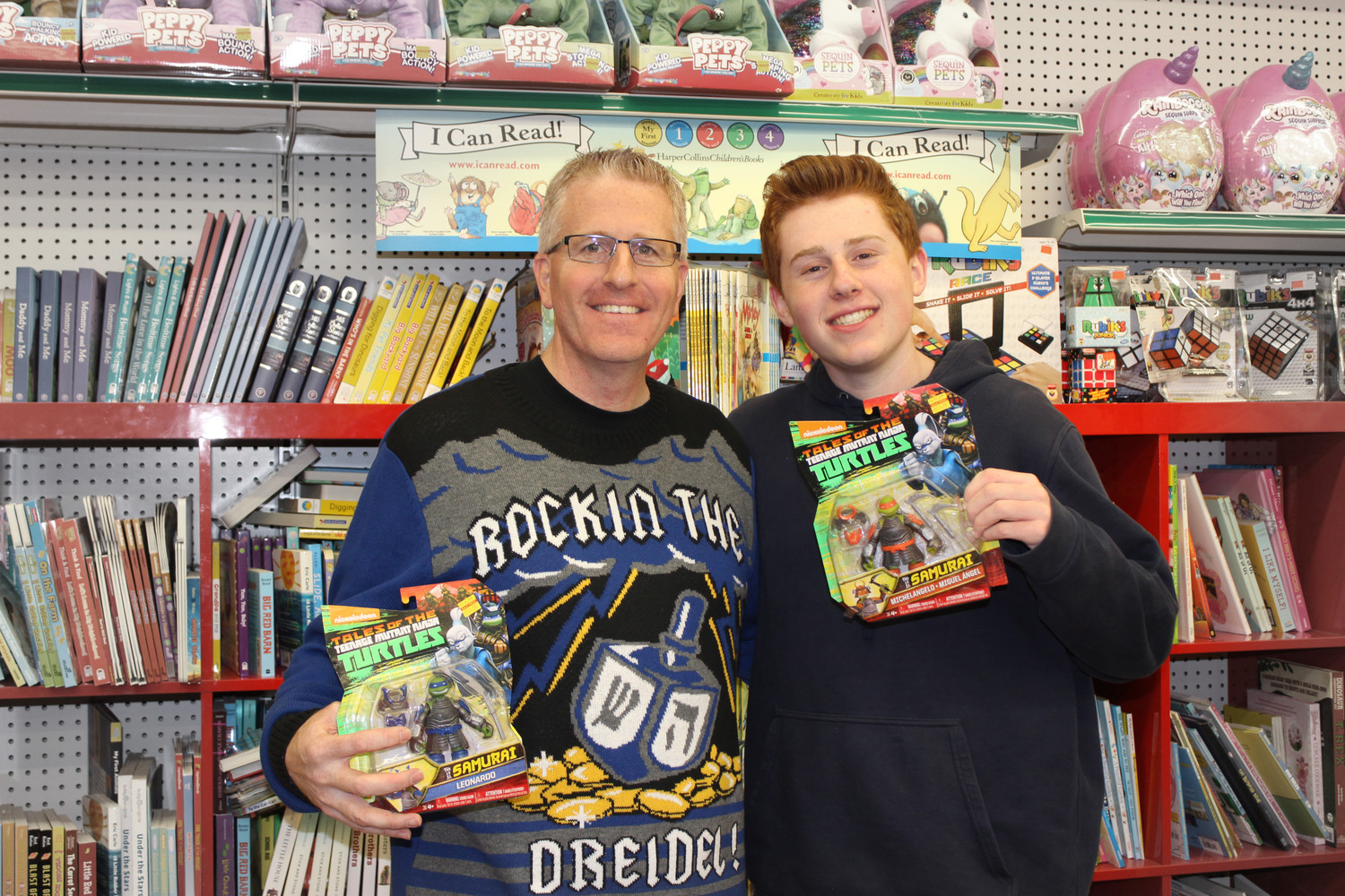Todd Weinstein, 46, and his son Alex, 15, with toys at Matty's Toy Stop in Merrick on Dec. 6 during a fundraiser, spearheaded by Weinstein, that donated $3,000 worth of toys to the John Theissen Children's Foundation.