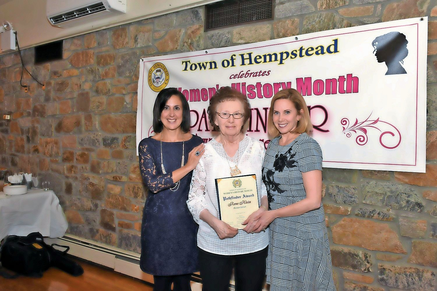Klein, 81, spends most of the year walking from business to business, collecting donations for her annual event, which supports local charities. Above, she received the Humanitarian Pathfinder Award by Town of Hempstead Supervisor Laura Gillen, right, and Town Clerk Sylvia Cabana.