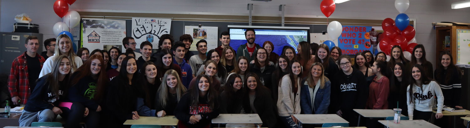 Shannon, center, with the Senior Experience class. The seniors helped raise $20,000 to give him a home in Illinois.