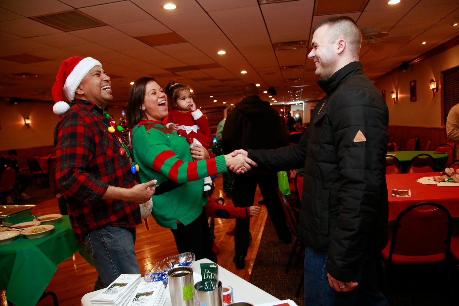"The East Meadow Chamber of Commerce and Enrique Reyna, 42, who serves in the Army and lives in East Meadow, hosted a holiday party celebrating local military personnel on Dec. 21 at the East Meadow Benevolent Hall. Reyna, far left, and 1st Sgt. Urbina Abarua welcomed Staff Sgt. Cory Krigbaum to what Reyna called ""a new Christmas tradition."""