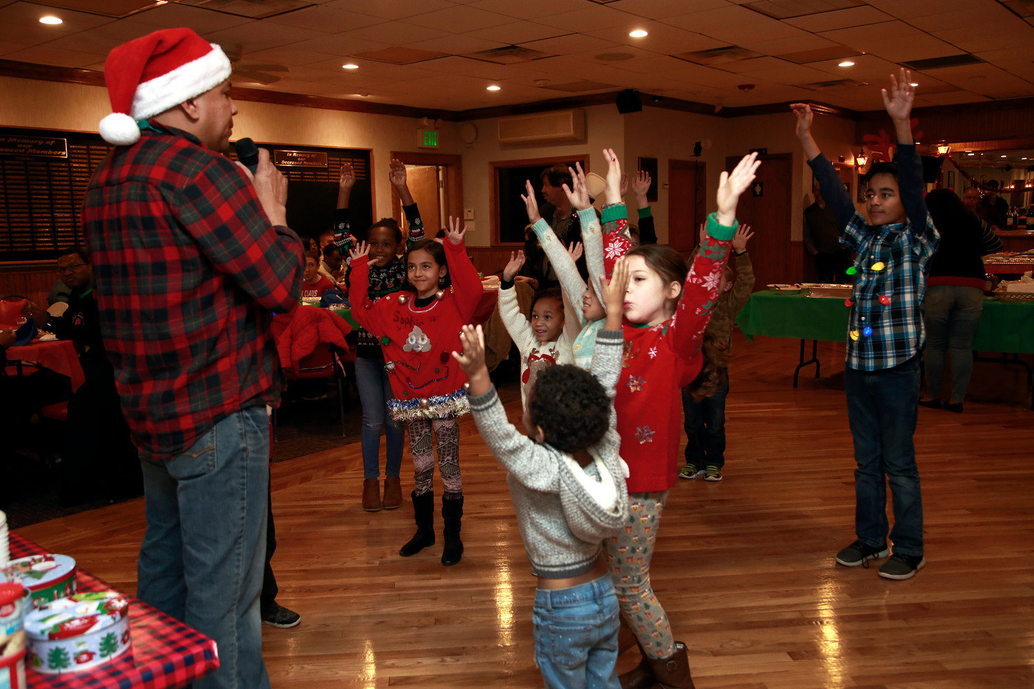 Sgt. 1st Class Enrique Reyna led children in a game of Simon Says while they waited to meet Santa Claus at the East Meadow Benevolent Hall on Dec. 21.
