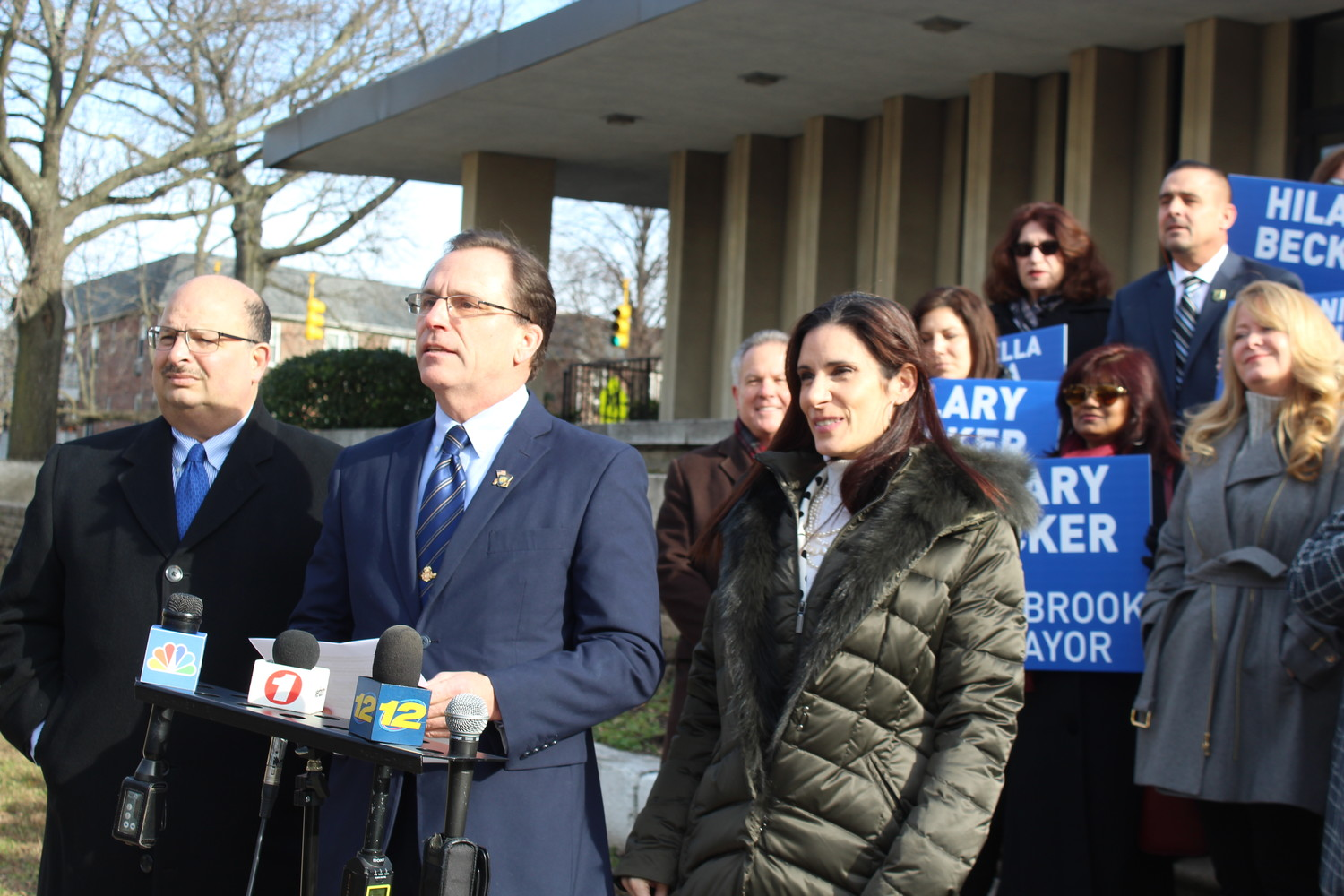 Lynbrook Deputy Mayor Hilary Becker, center, announced his candidacy for mayor at a news conference outside Village Hall on Jan. 2. He will challenge incumbent Alan Beach in the March 19 village election. Steve Ligouri, left, and Antoniella Tavella are running for trustee seats.