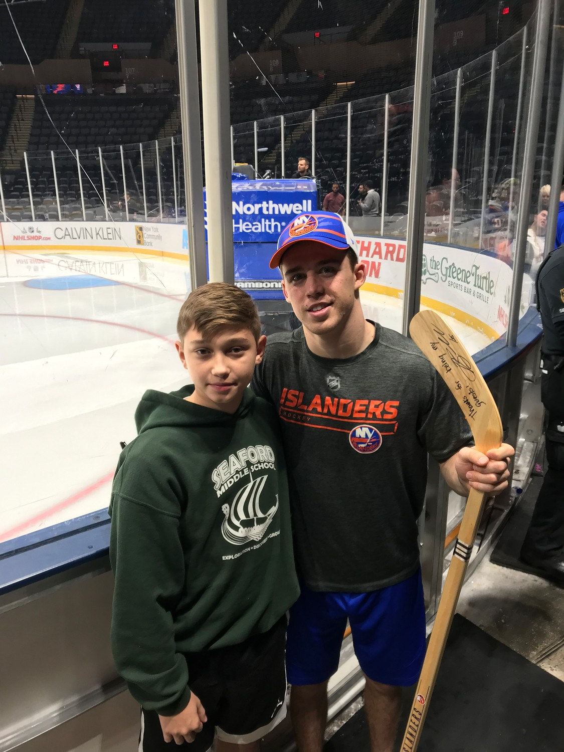 Anthony Beauvillier, right, has been working with the Alzheimer's Association since December 2017, a month before his grandfather Jean Cardin died after having the disease for roughly five years. Beauvillier invites caregivers and families impacted by the disease to each Islanders home game for a meet-and-greet. After the Dec. 10 game at Barclays Center in Brooklyn, he signed an autograph for Frank Pyryt, 13, of Seaford.