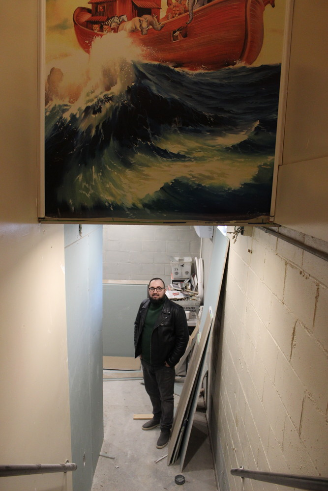 Above a staircase leading to the basement is a vibrant painting of Noah's ark. Below, a construction crew has been renovating the space to make more room for storing food.