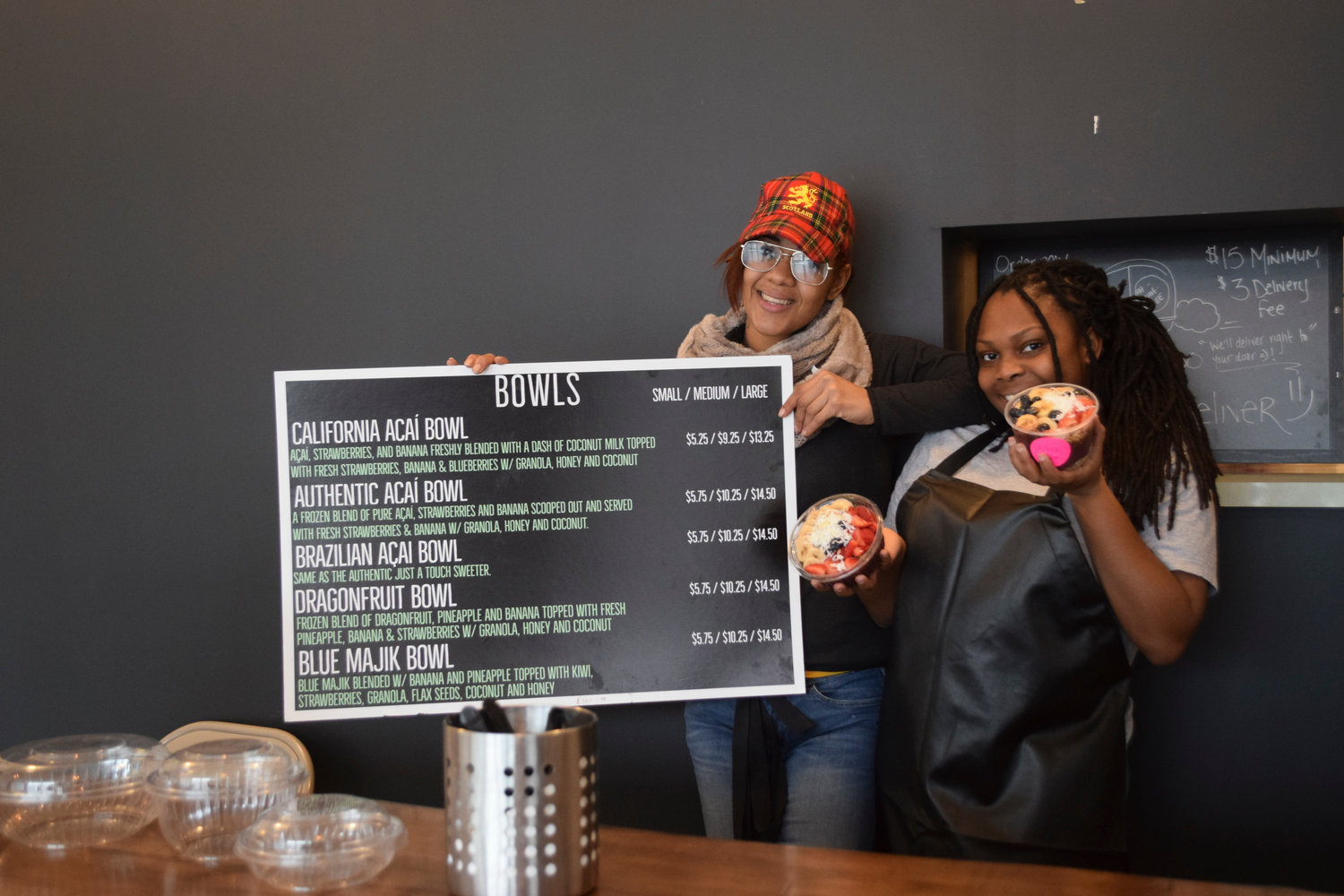 Ah-Sah-EE crew members Alycia Mason, left, and Shilea Scott with the menu and the California and Brazilian Acai bowls.