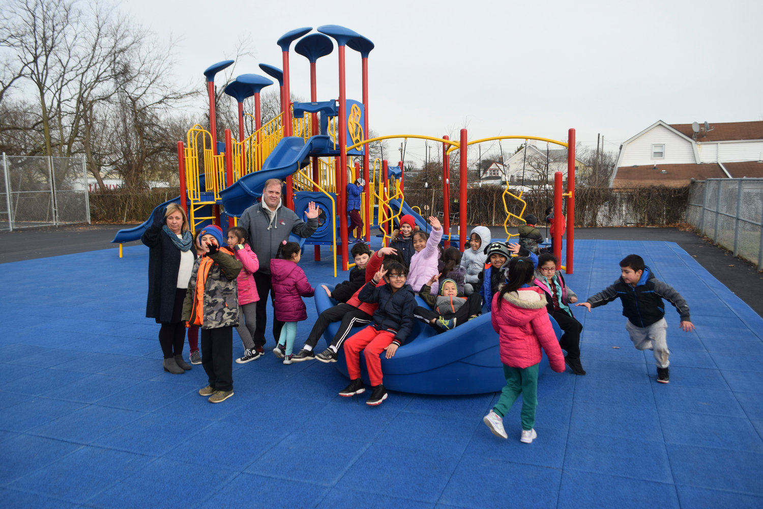 Lawrence Primary School second-graders love the new playground and especially the merry-go-round. Principal Christine Moore is at the far left along with physical education teach Don Makofske.