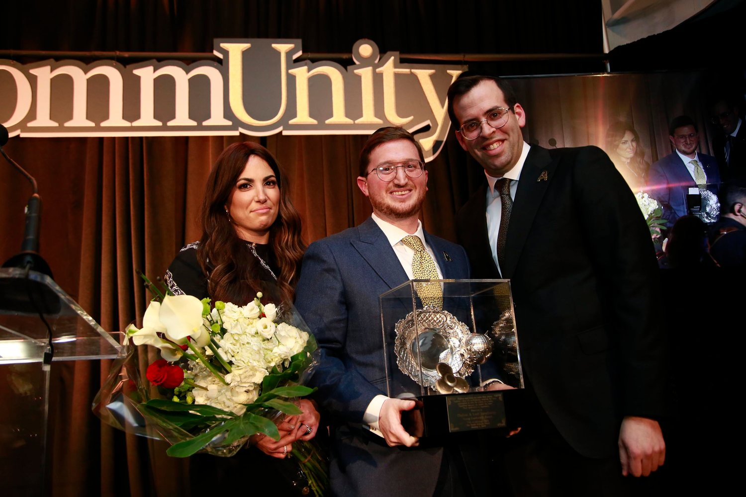 Achiezer's Young Leadership Award was presented to Leah and Shalom Jaroslawicz by Rabbi Boruch Bender, right.