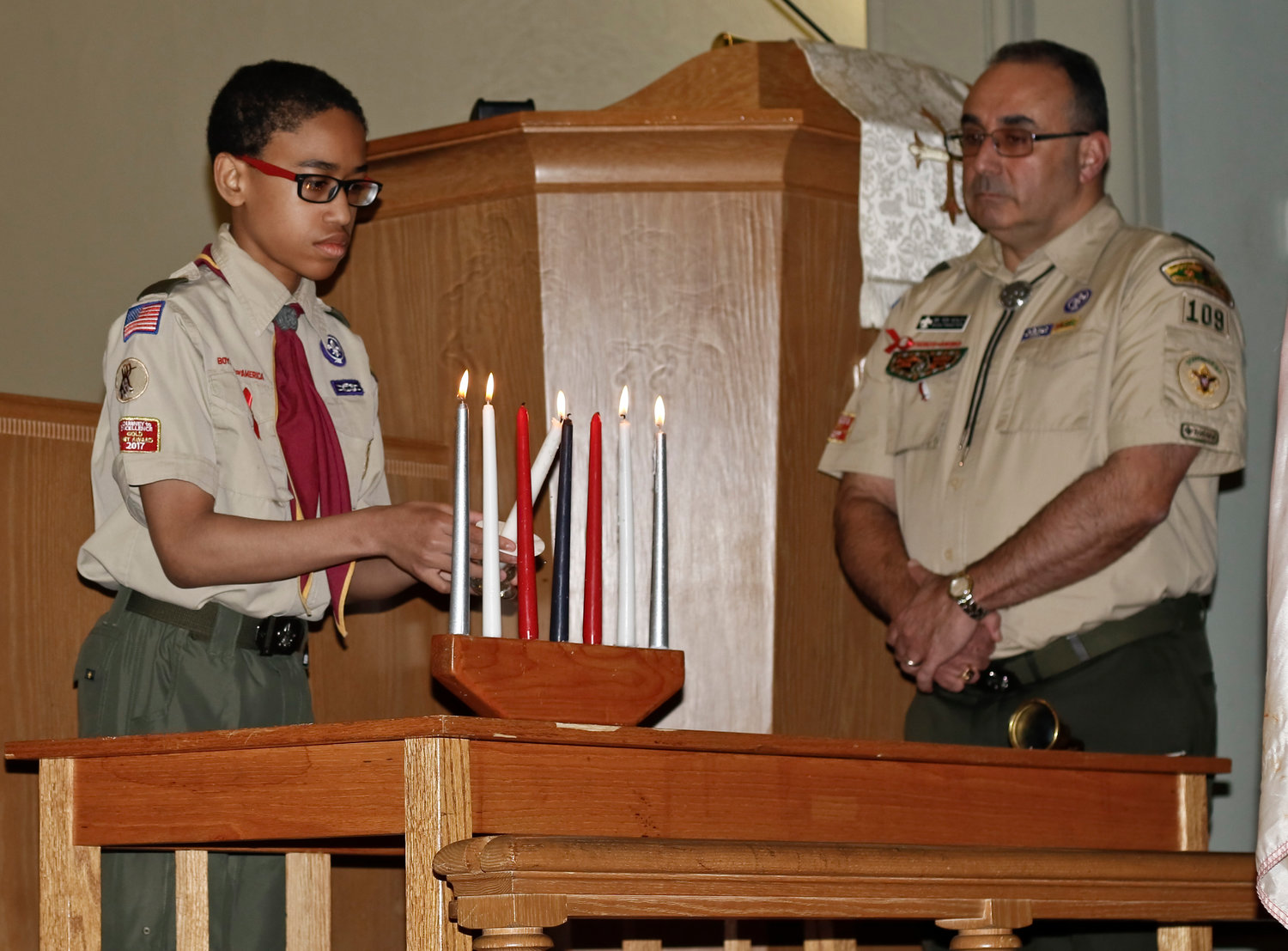 During a reading about the significance of the Eagle Badge, scout Shawn Redhead lit the red candles.