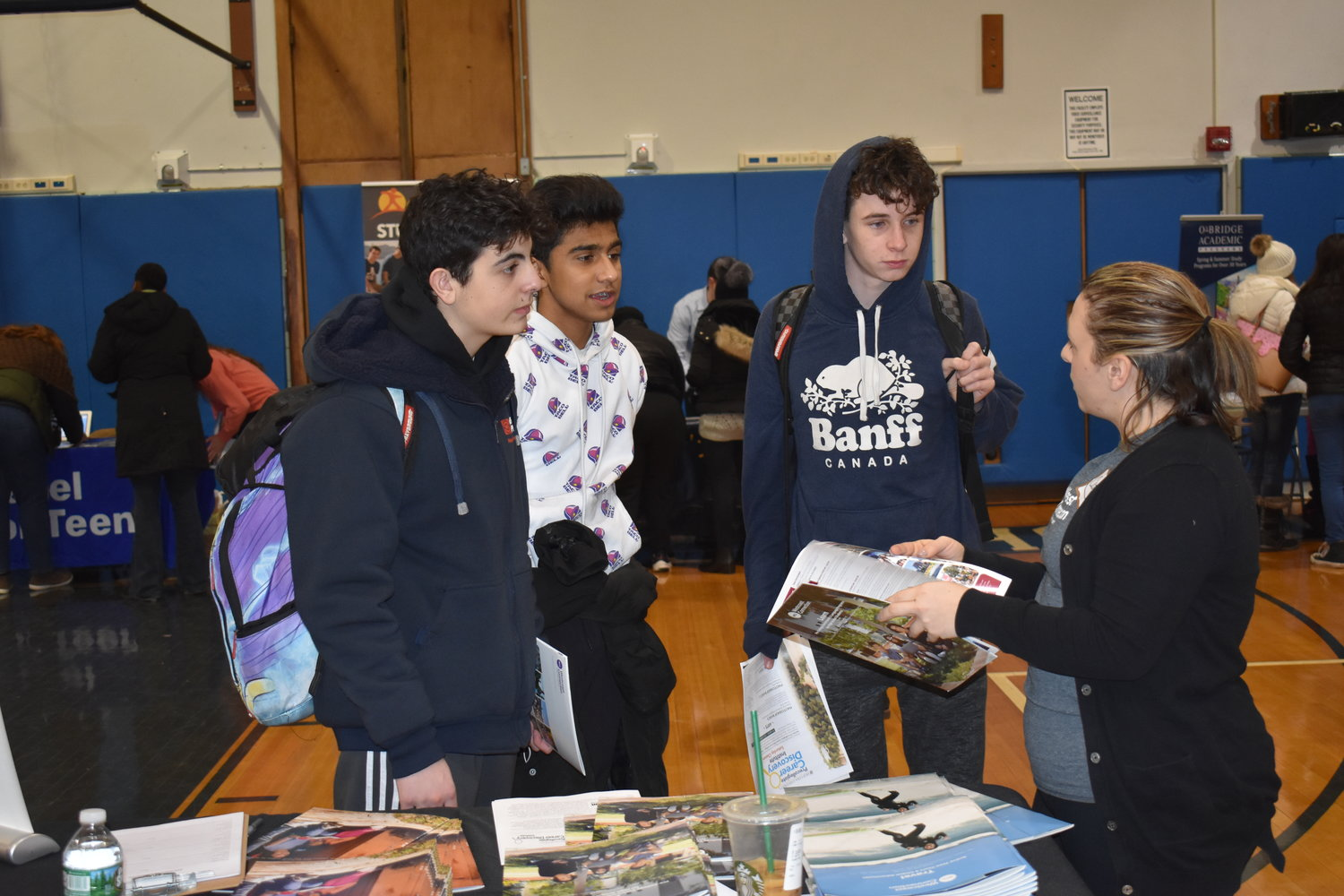 Ninth-graders Justin Shnayder, left, Bilaal Sadiq and Noah Tipipere discussed West Coast Connection, a student travel program, with Catherine Montera, a trip director.