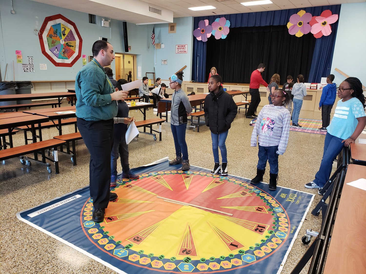 Adelphi University student-teacher Thomas Simonetti taught fourth-graders Rebecca Fraser, Ayana Akinsile, Tayshawna Williams and Paula Dean how to read time on an analog clock.