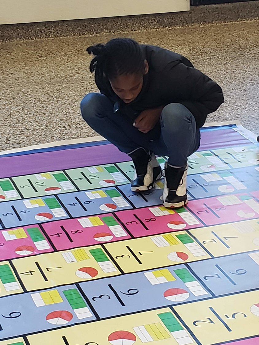 Fourth-grader Ayana Akinsile, below left, concentrated on finding fractions' common denominators while she hopped around the fraction mat.
