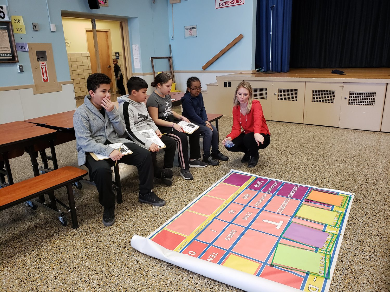 Leo F. Giblyn School fourth-graders, from left, Johnny Nunez, Kenneth Reinoso, Angelina De Los Santos and Owen Bruce listened as Jahn Corbo, the school's math specialist, explained the rules and objectives of the place value mat on Monday.