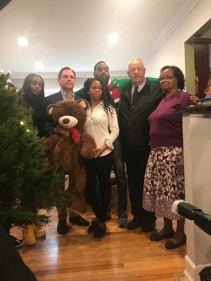 Freeport Mayor Robert Kennedy, second from right, and Lynbrook Deputy Mayor Hilary Becker, second from left, shared Christmas Eve with the Easy family, Caitlin, left, Nixtia, Marcus and Ruby Taylor, right, as a show of support as they waited for Norman Easy's body to be returned to New York from China.