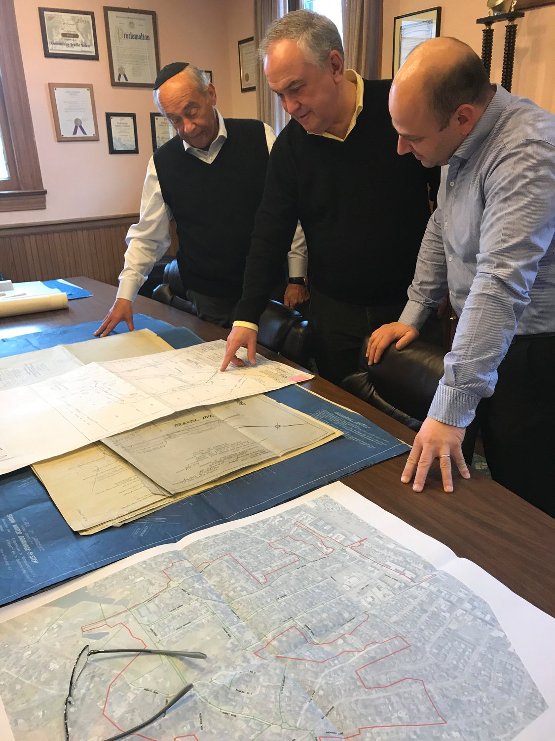 Lawrence Mayor Alex Edelman, far left, reviewed stormwater infrastructure maps with LKMA Senior Project Director Gilbert Anderson and Deputy Village Administrator Gerry Castro.