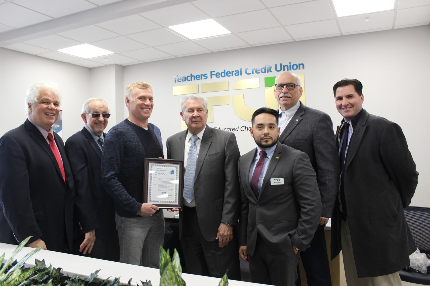 Robert Allen, the president and chief executive officer of TFCU, fourth-from-left, joined at its ribbon cutting with Tim Southerton, the chairman of the board, left; Ray Grossman, the board director; Michael Levy, the incoming president of the East Meadow Chamber of Commerce; Andres Silva, the branch manager; Councilman Dennis Dunne Sr., a Republican from Levittown, and Matthew Hynes, a representative of Town of Hempstead Supervisor Laura Gillen.