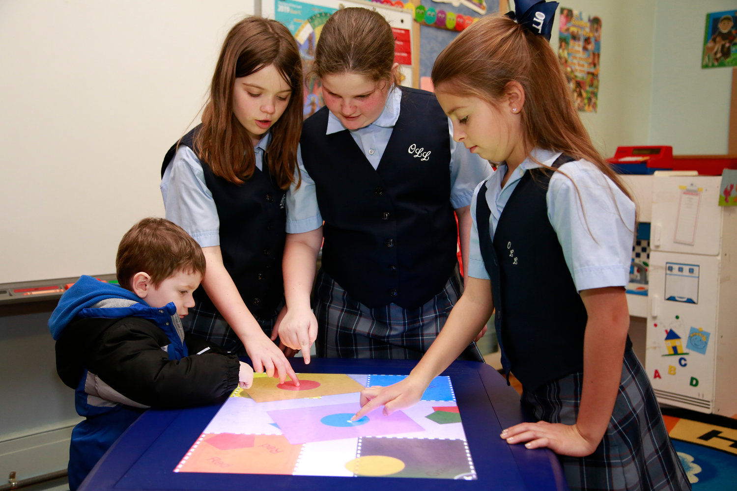 5th graders Gabriella Lackner, Victoria Lackner and Kayla Prizzi show 3-year old Joseph Lackner how to use the Nursery class smart table.