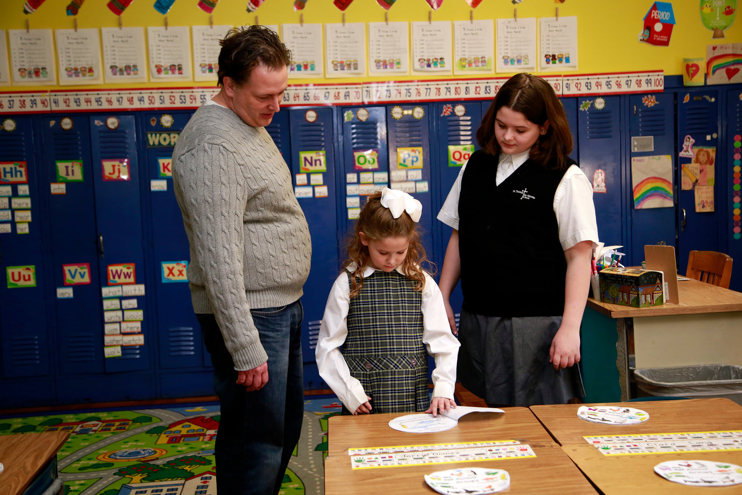 First-grader Ella Harding showed her father — Mike, and her older sister, Kiera — her project on animals.