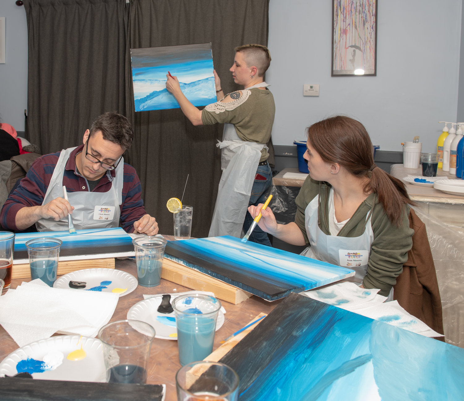 Chris and Jennifer Mosera, sitting, made sure to model their paintings after instructor's Darya Gauthier, center, example.