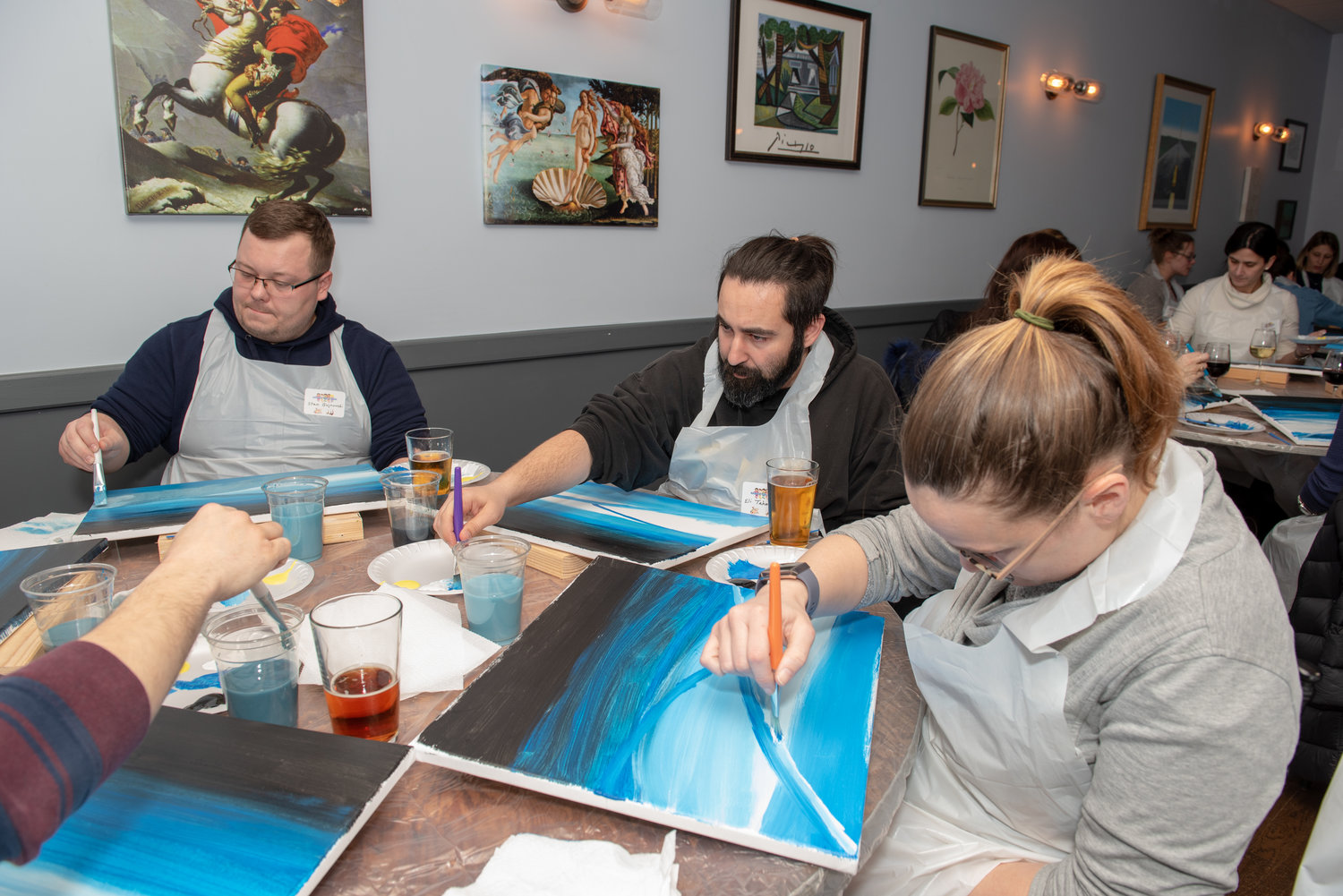 Stan Bujnowski, left, and Eli and Michelle Tahmasebi focused as they painted.