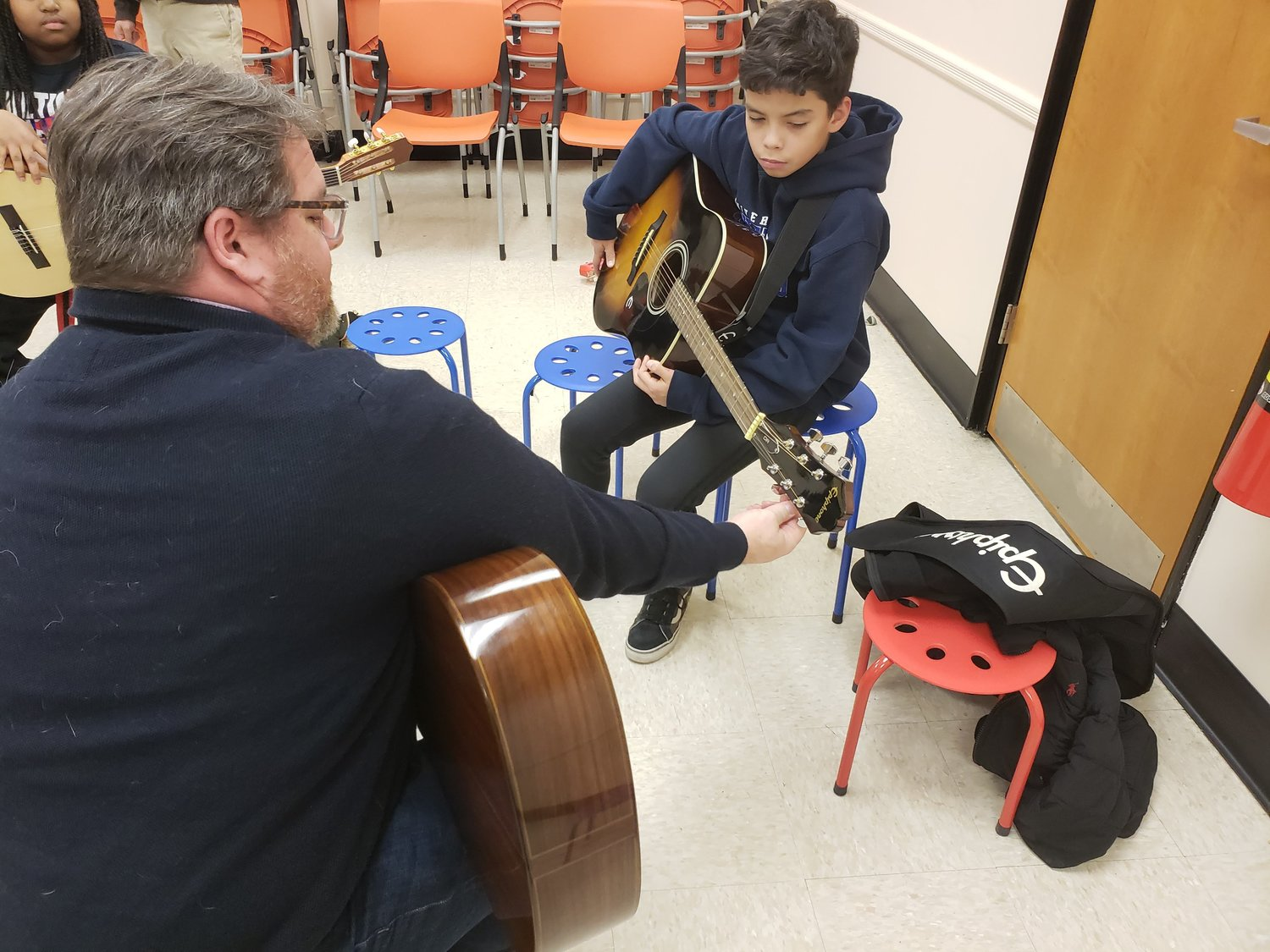 instructor Chris Gotzen-Berg, of the Legato Foundation, helped Kirstian Herandez, 11, tune his instrument.