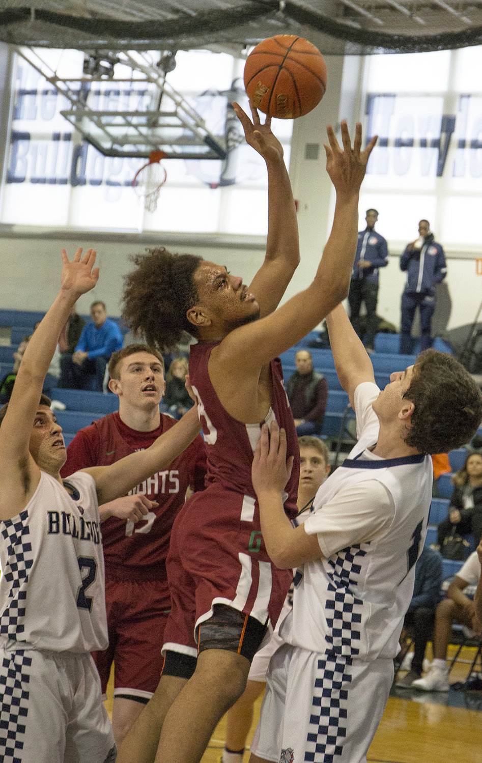 Glen Cove's Gio Mendez, center, did some work in the paint during the Big Red's 71-63 setback at Hewlett last Saturday.
