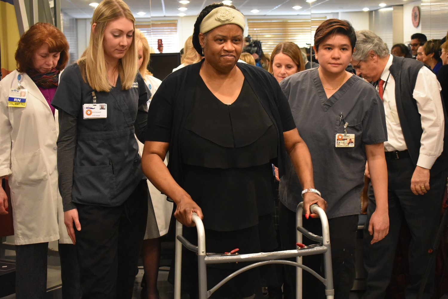 Patricia Lewis, of Rockville Centre, who had both legs amputated due to complications of undiagnosed diabetes, walked on prosthetic legs at Lynbrook Restorative Therapy and Nursing on Jan. 31, before returning home. Therapists Arielle Whitehall, left, and Tan Pilapil joined her.