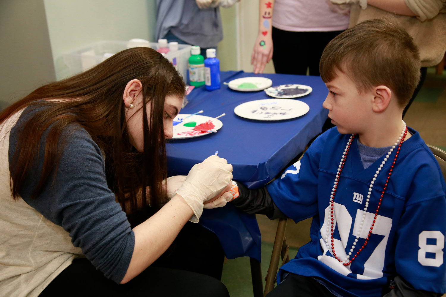Oceanside High School Key Club member Katie Buhse painted a tattoo on Giants fan Ryan Horbach.