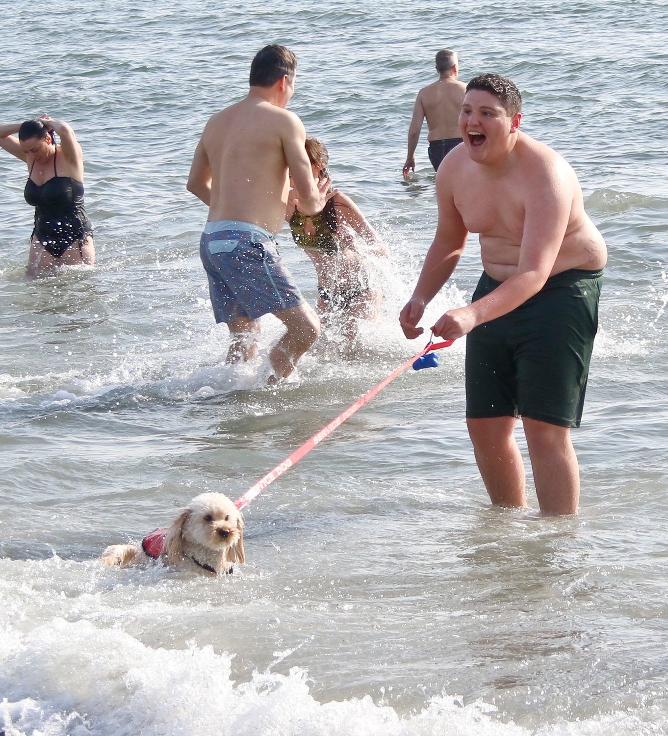 Juston Cornell, also of Long Beach, ran into the water with service dog Peaches.