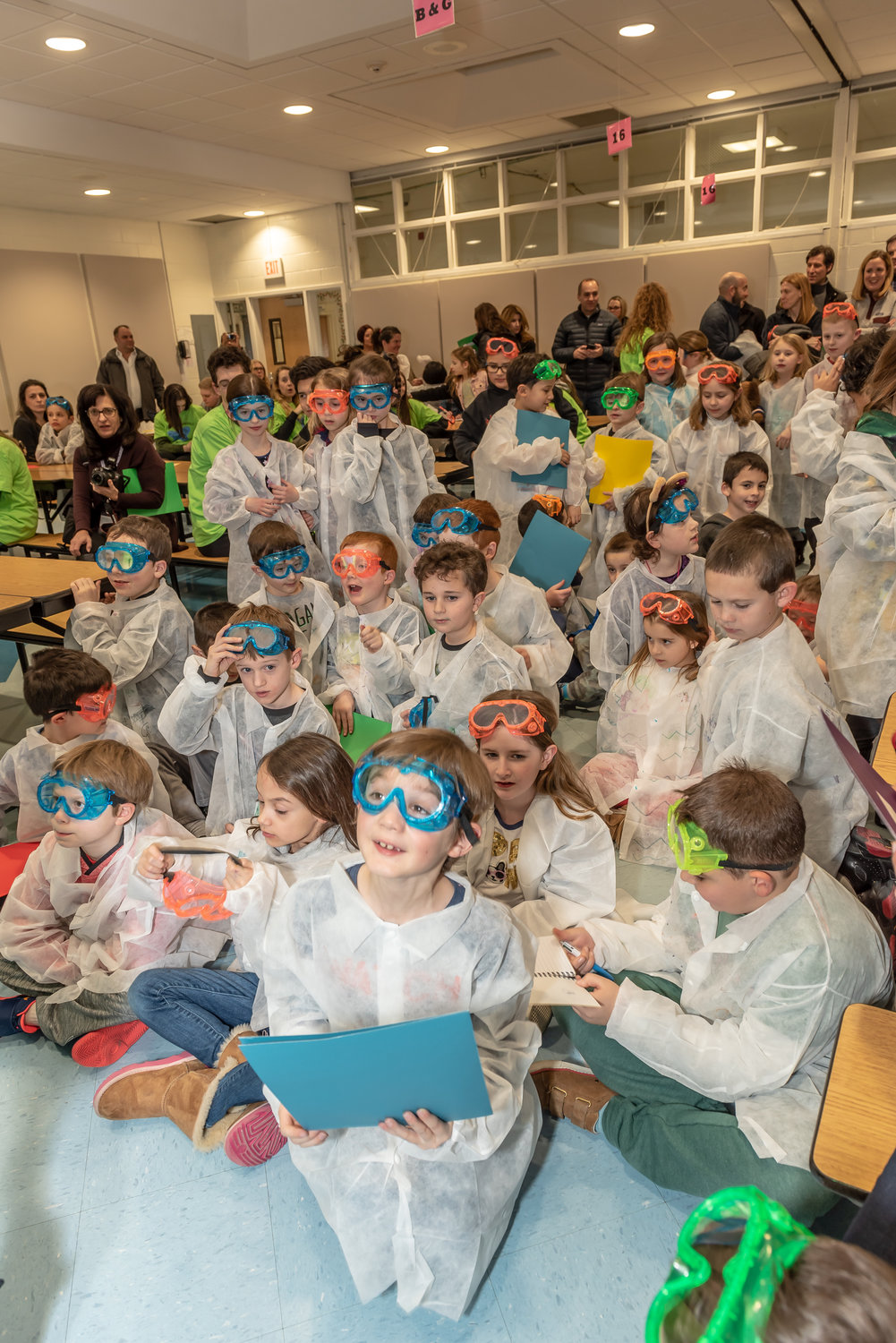 Wearing goggles and lab coats, the young scientists watched a video on scientific processes.