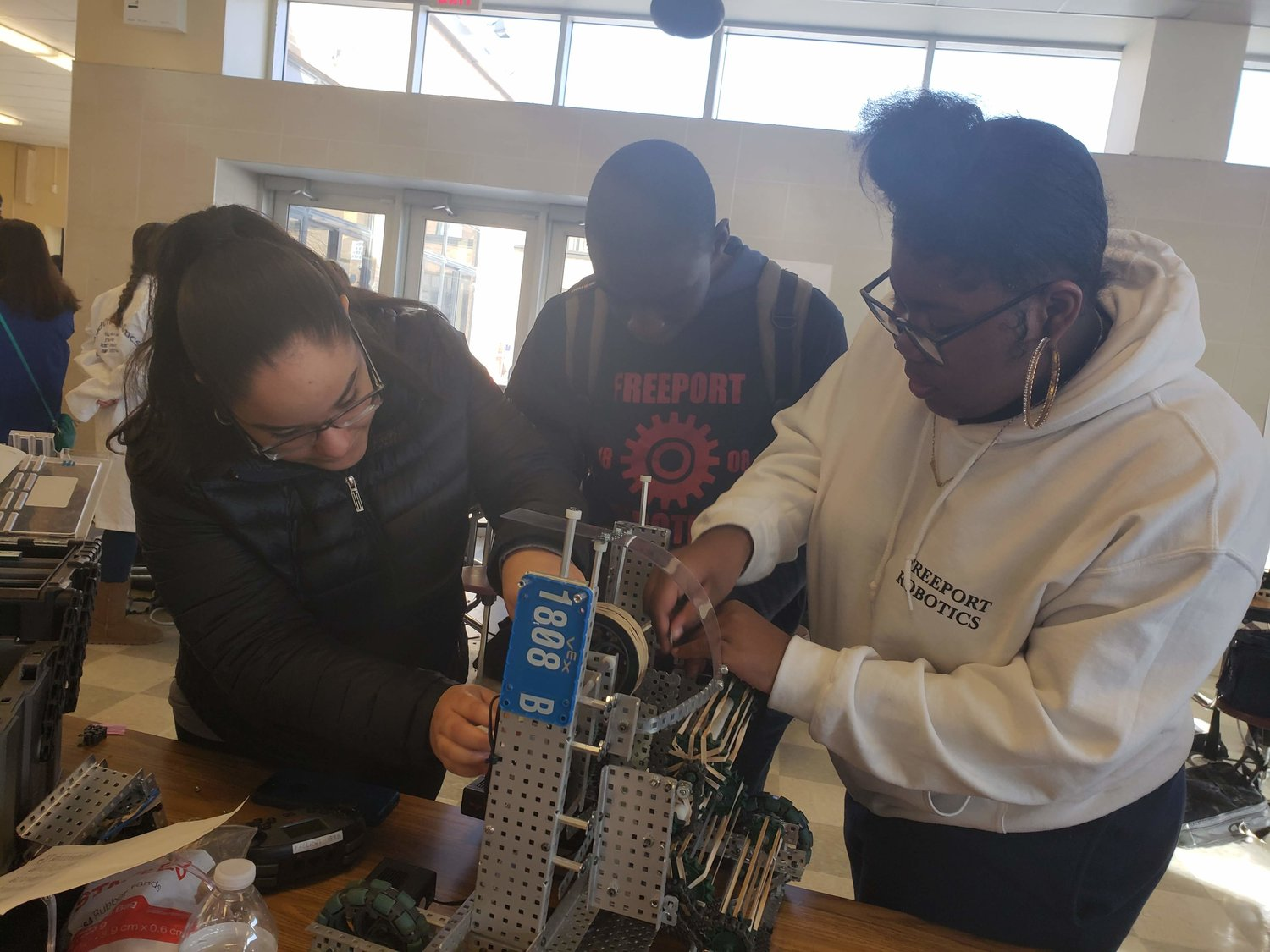 Freeport High School junior Yenifer Tiburcio-Jerez, 16, far left, helped her teammates, junior Mason Bazemore, 16, and sophomore Diamond Anderson, 15, make last-minute adjustments to their robot before the next battle round at the fifth annual Robotics Competition at FHS last Saturday.