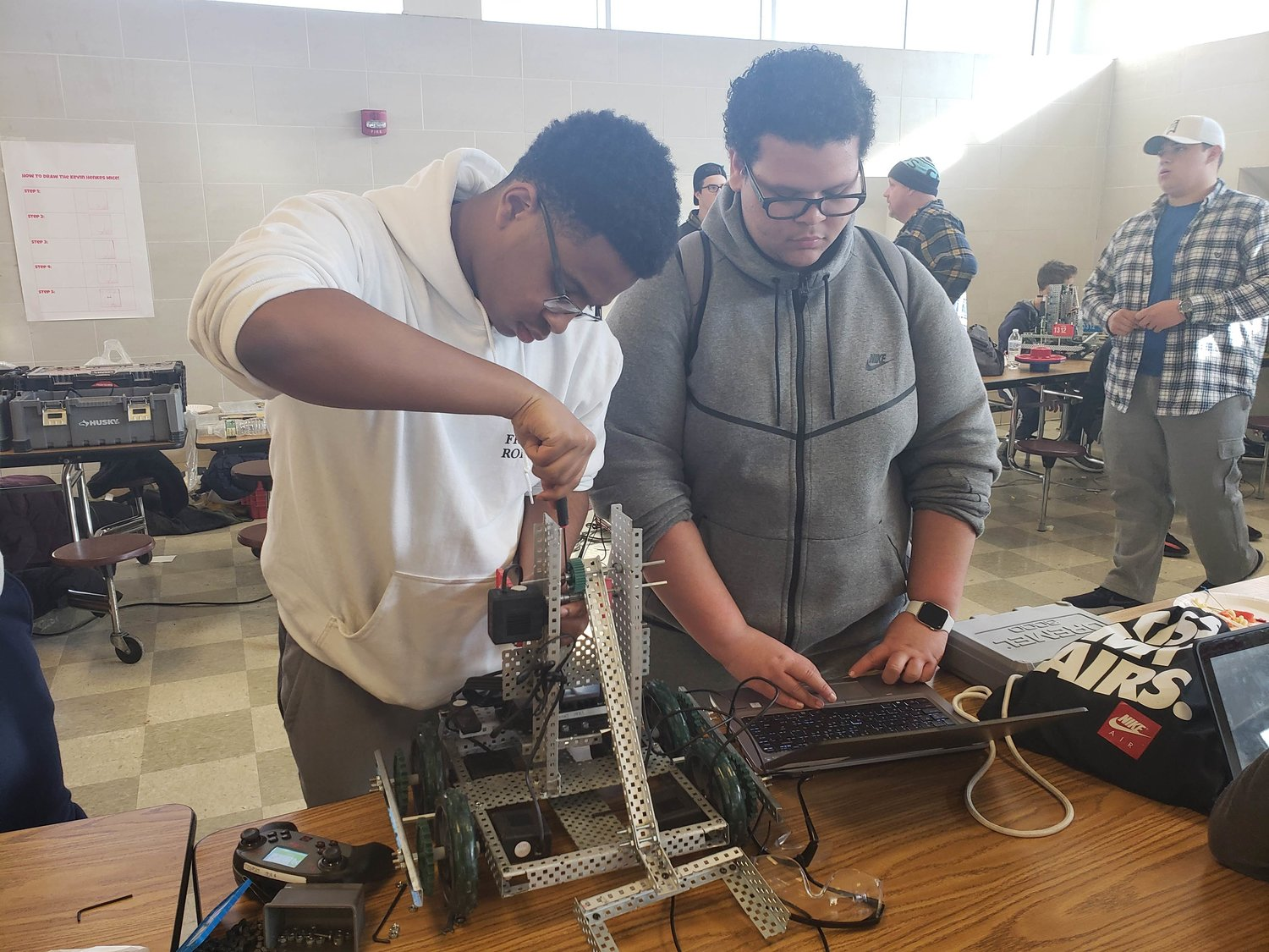 After finishing a battle round, junior Ola Aroso, 16, left, fixed a robot, while sophomore German Cerrate, 15, reviewed its software.