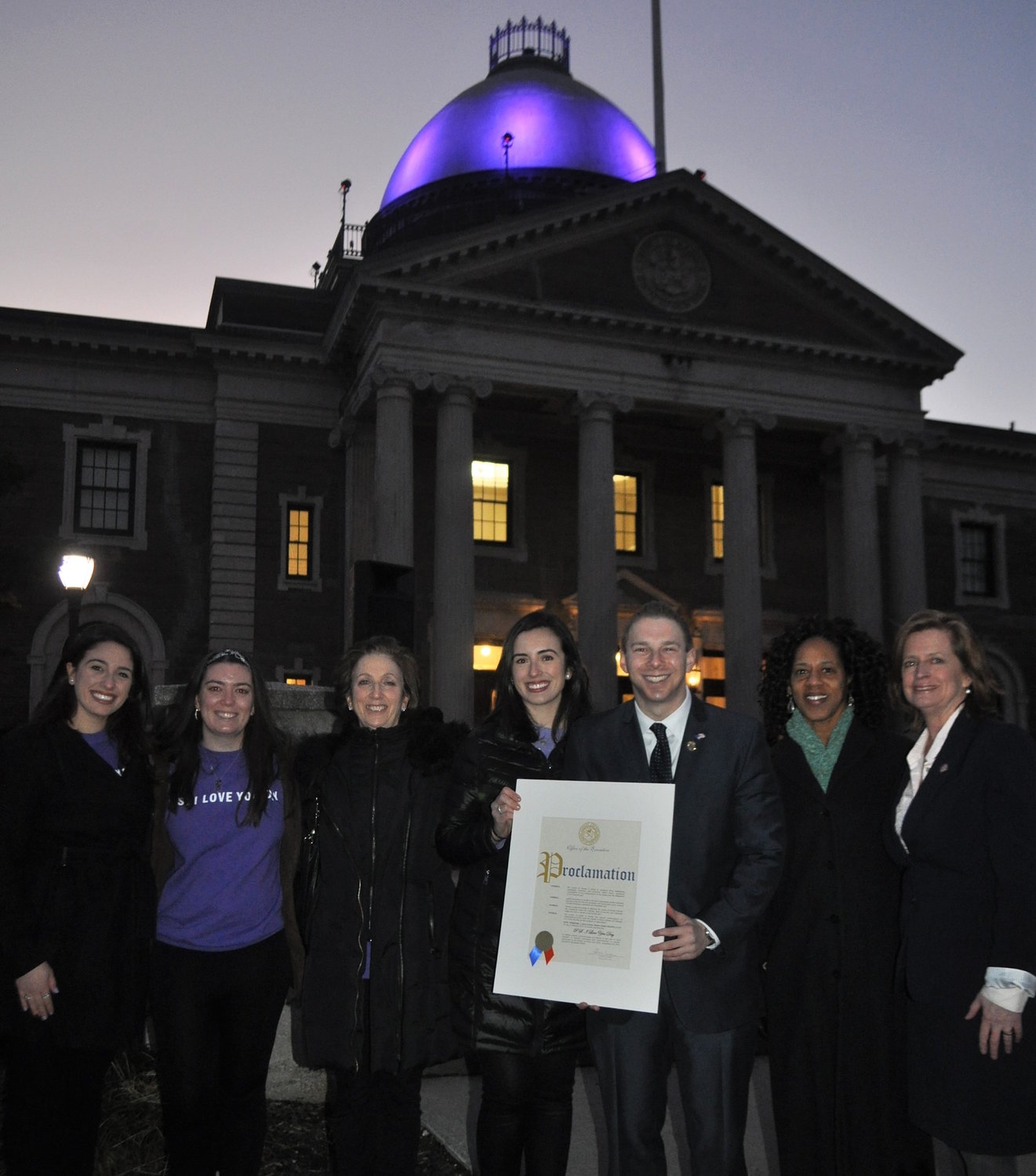 Legislator Josh Lafazan and other Nassau County officials met with P.S. I Love You Day founders Brooke DiPalma, left, and Jaimie DiPalma, center, to light the dome of the Theodore Roosevelt Executive and Legislative Building in Mineola to increase suicide awareness. The dome shone purple, the color the foundation has adopted.