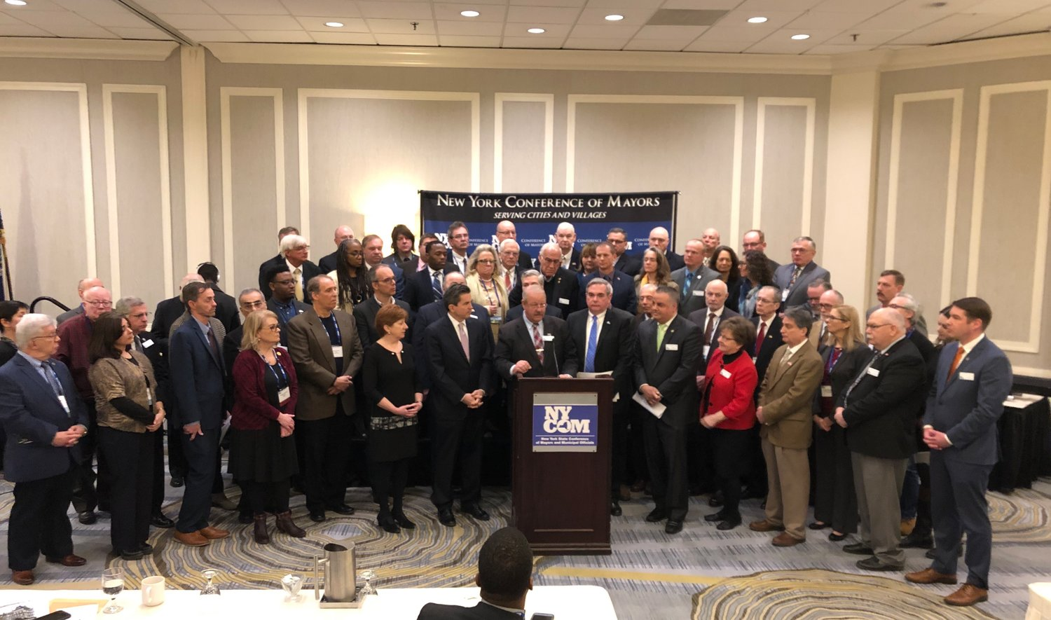 Mayor Robert Kennedy, at the lectern, was joined in Albany on Monday by 540 mayors from across New York demanding that Governor Cuomo restore Aid and Incentives for Municipalities funding.
