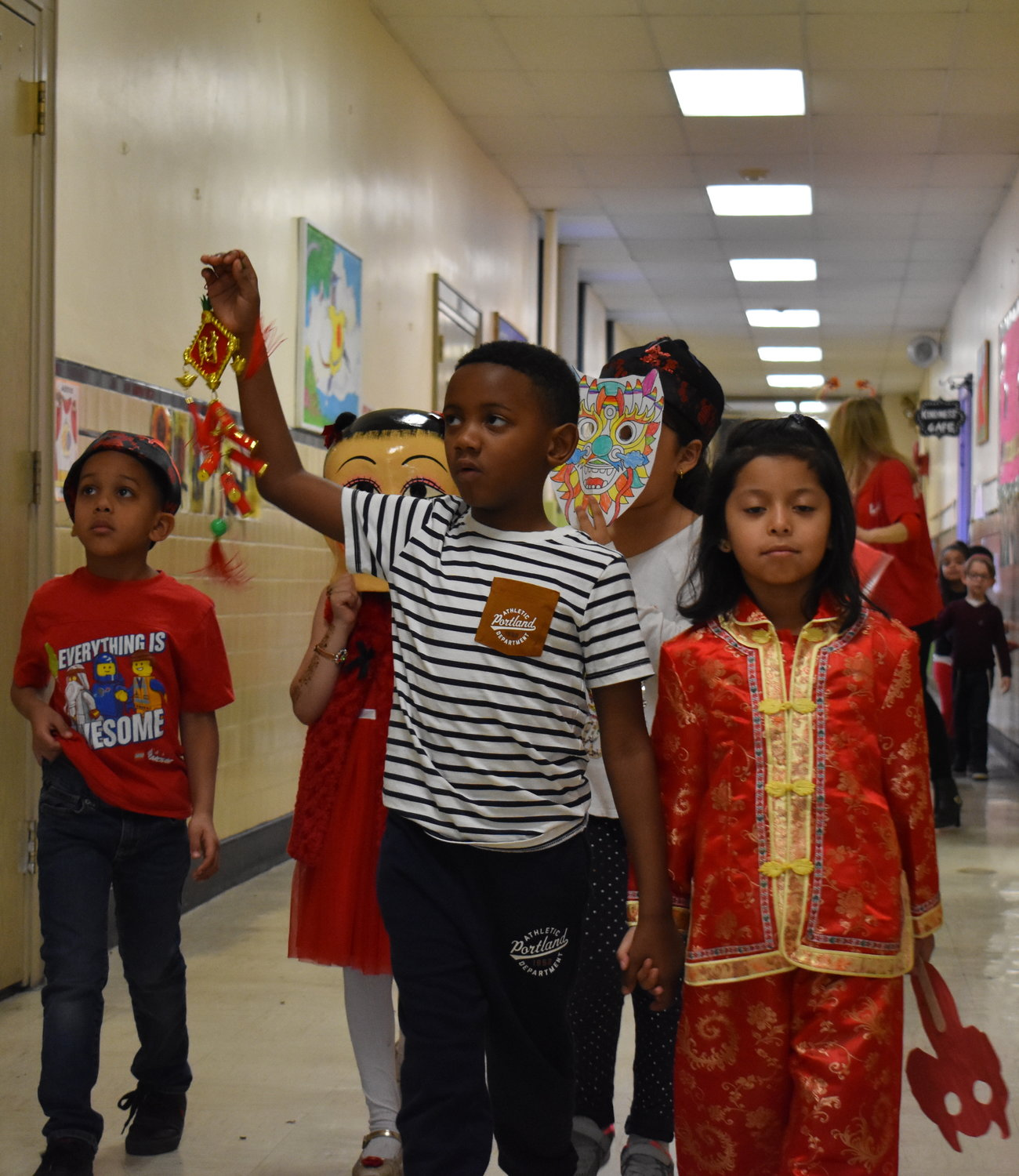 Kindergarten and first- graders with traditional decorations, hats, masks and outfits led the parade through the hallways. From left, kindergarteners Andrew Chandler and Seliena Sharhan, first-graders Ashton Gardner and Isabella Tenecela and kindergartener Angelina Segovia.
