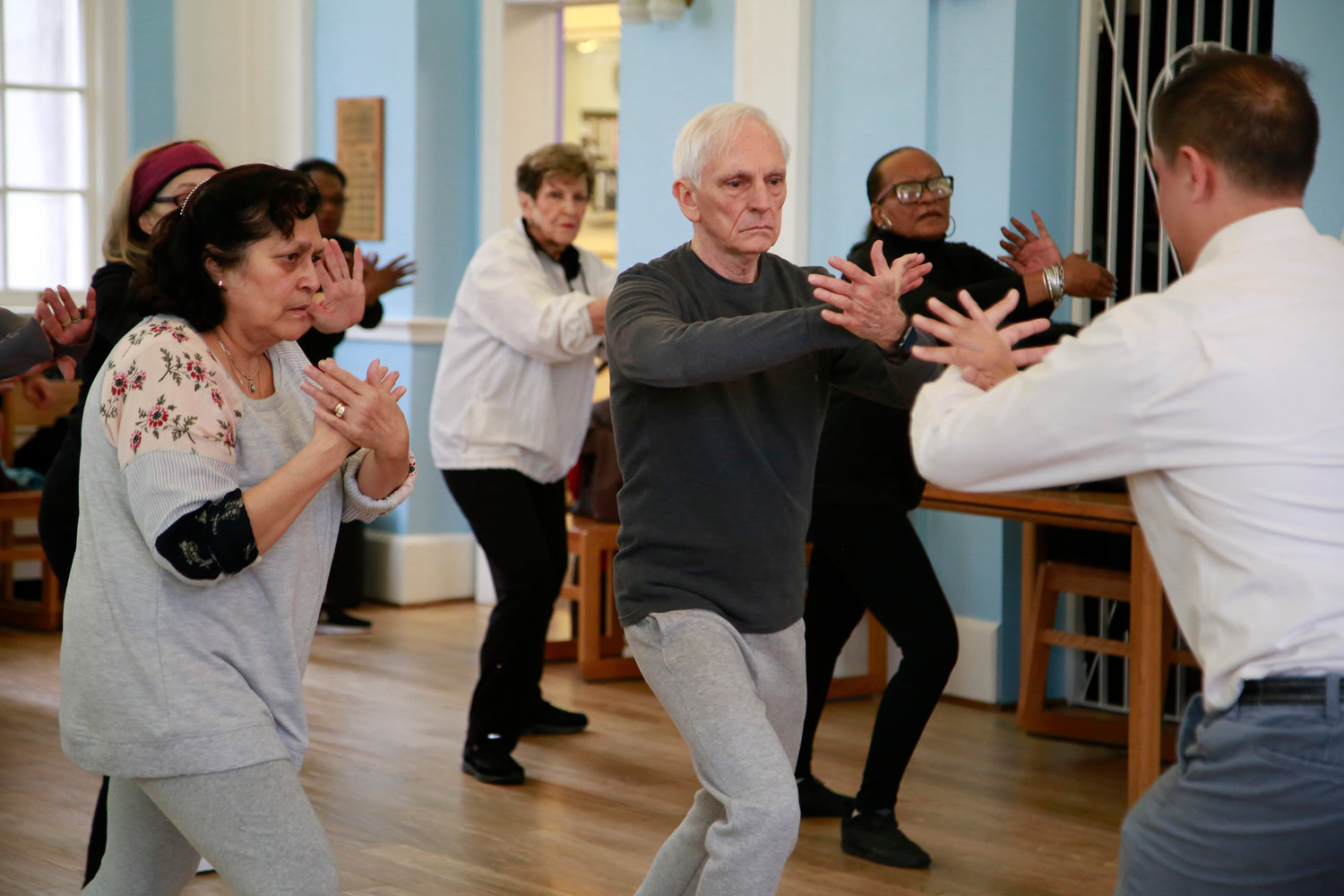 Tai chi students, Olga Marrell, left, and George Perfetto follow instructions during the ward off movement.