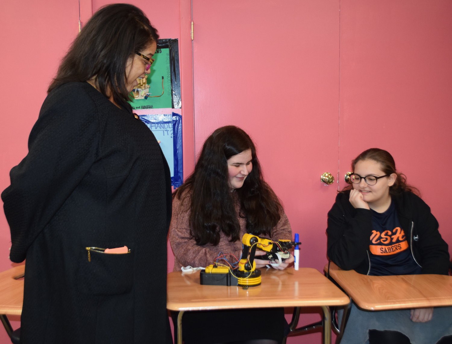 State Assemblywoman Michaelle Solages was impressed by the robotic arm built by MSH sophomores Ayala Terebelo, center, and Emily Weintraub.