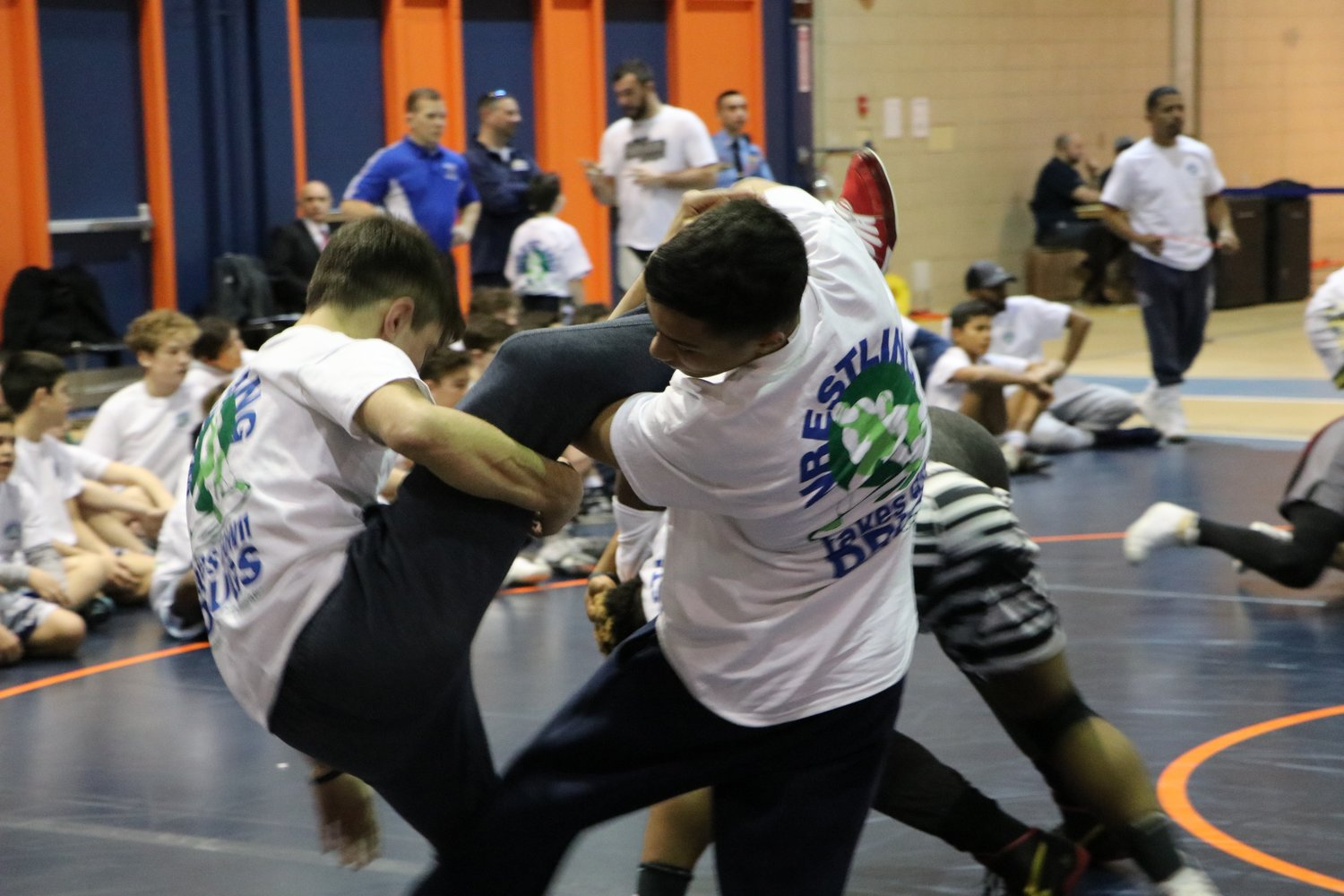 A teenage wrestler looked to sweep the leg of his opponent and bring him down to the mat for a pin.