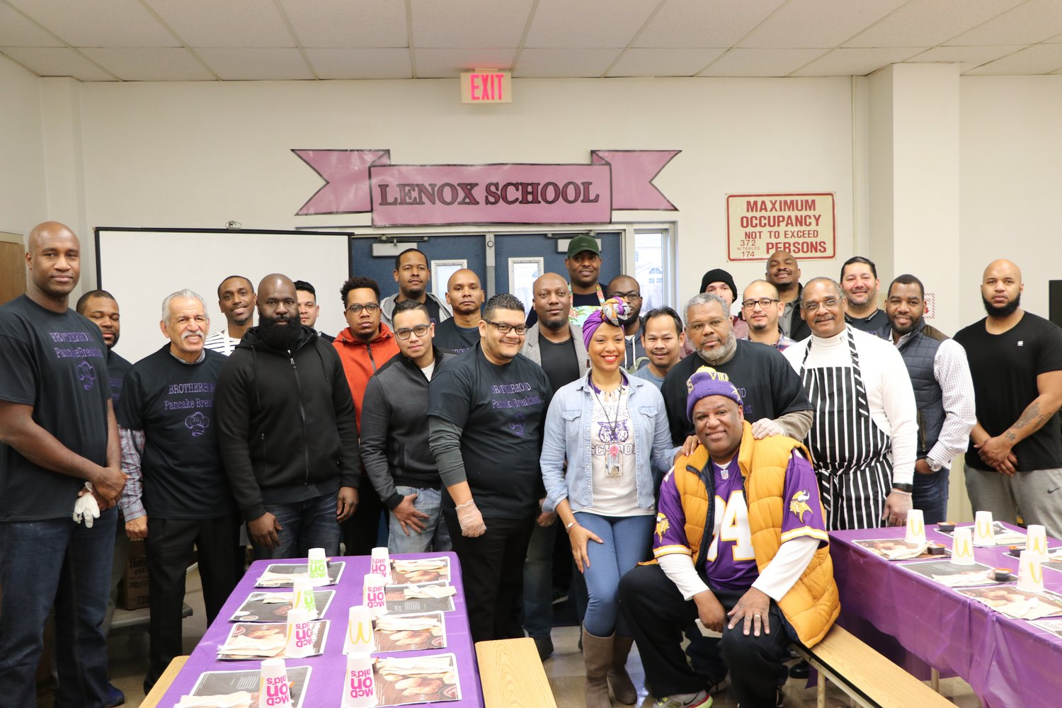 Lenox Principal Asheena Baez, center, with the fathers, uncles and grandfathers of Lenox students and alumni.