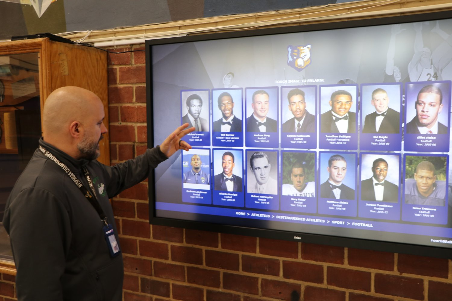 Ed Ramirez, Baldwin's athletics director, shows off the screen with highlights of past Baldwin sports stars
