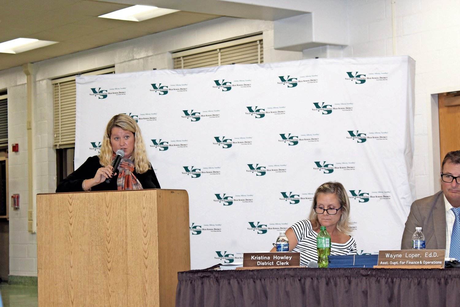 Lori Lang, left, spoke about the need for after-school busing for private school students at a Board of Education meeting in October.