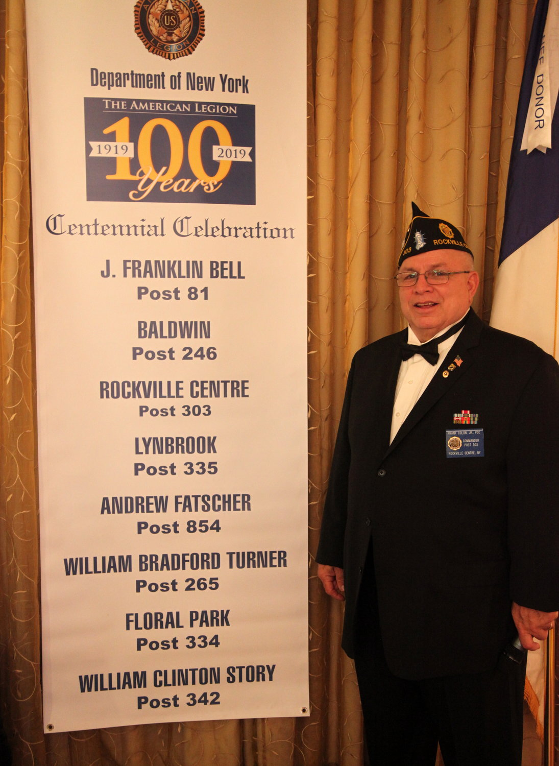 Post 303 Commander Frank Colon, with the event banner.