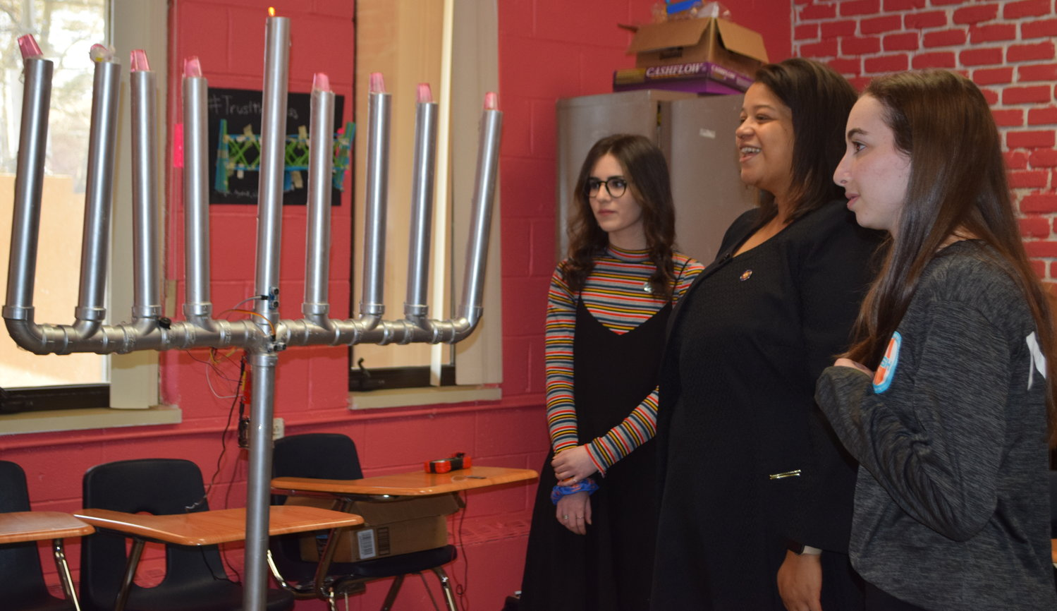 Combining religion and science, juniors Tal Galon, left, and Avigayil Roffe demonstrated their musical Hanukkah menorah for State Assemblywoman Michaelle Solages.