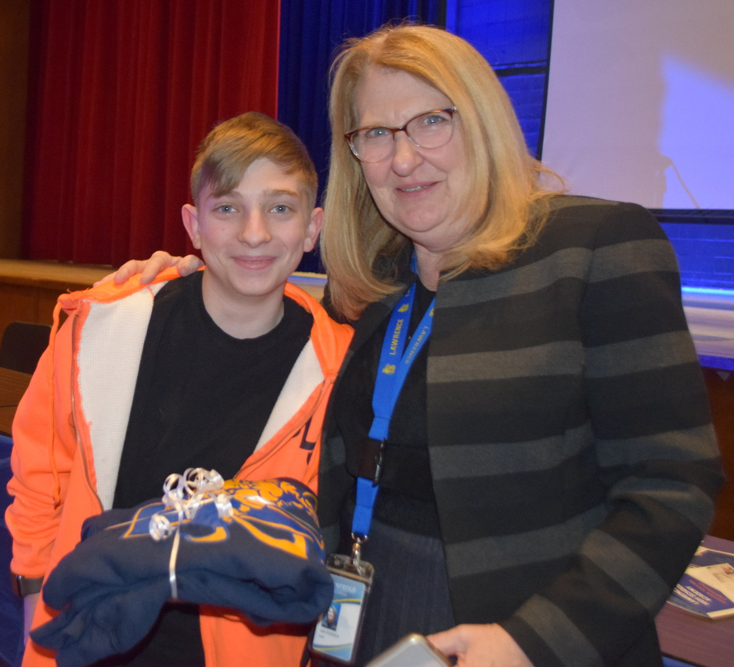 Lawrence High School freshman Brandon Rebel received a sweatshirt with the Golden Tornado mascot inscribed on the front from Superintendent Dr. Ann Pedersen for his work on the updated district website.