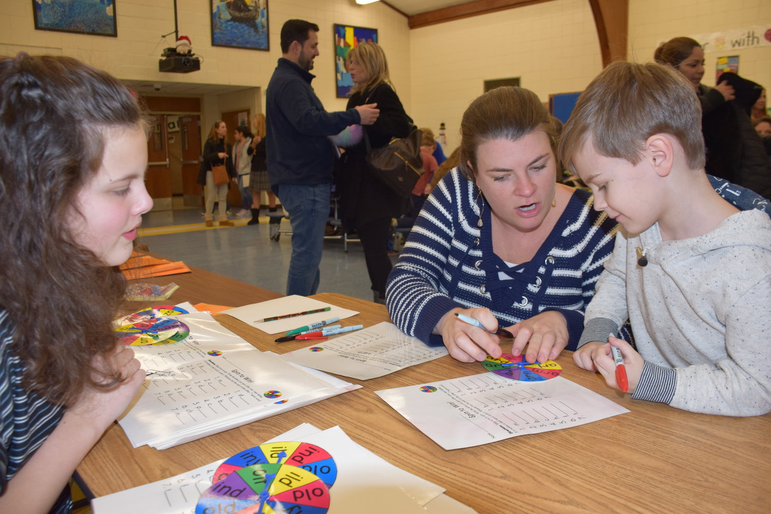 Middle School student Abigail Maselli, left, said she enjoyed teaching her game to parents and students, who included Rebecca Carfora and her son, Alfred, at Bayville Primary's Family Math/ELA Night.
