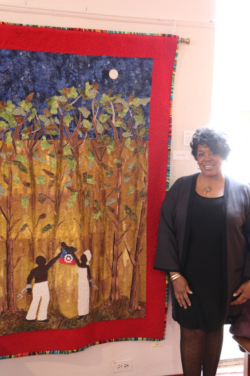 "Kim Taylor with her quilt ""Juneteenth,"" representing the day the United States abolished slavery, one of her many creations on display at Freeport's South Nassau Universalist Congregation."