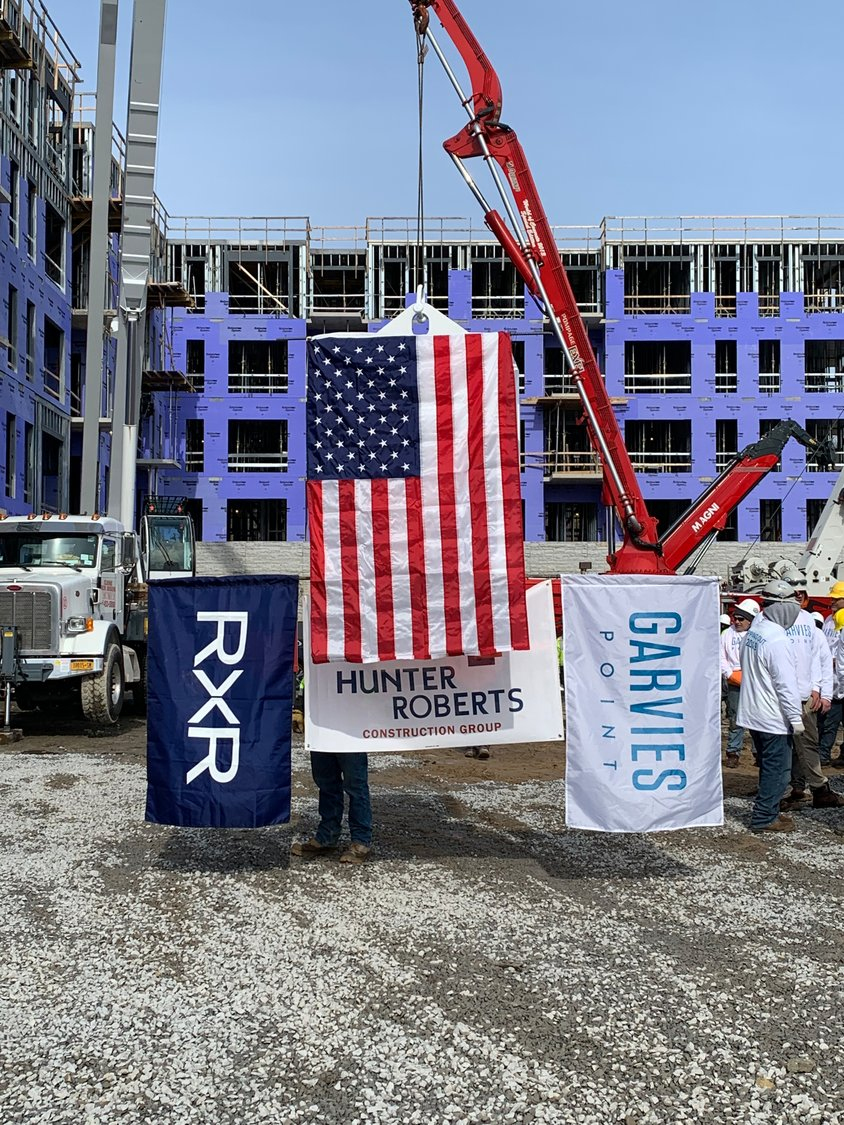 A symbolic block of cement adorned with the American flag and the companies involved in the construction at Garvies Point was lifted by crane onto the top of the Beacon to celebrate the topping off.