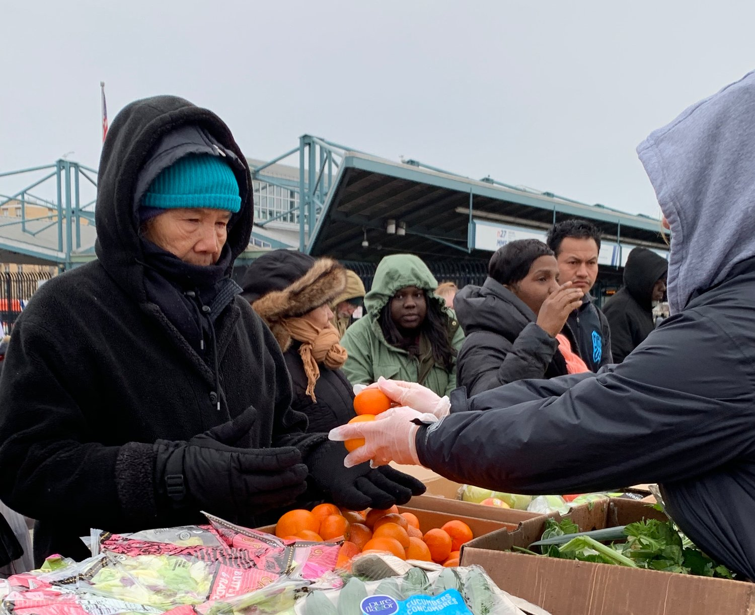 A volunteer handed out food to a person in need recently at Community Solidarity's Food Share at the Long Island Rail Road station.