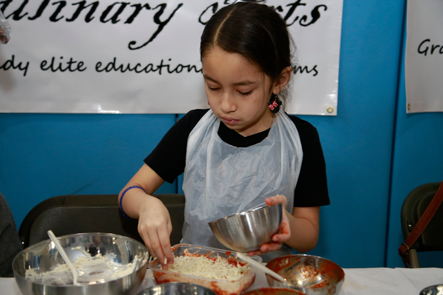Kiara Ayala, 8, sprinkled shredded mozzarella cheese on her lasagna.