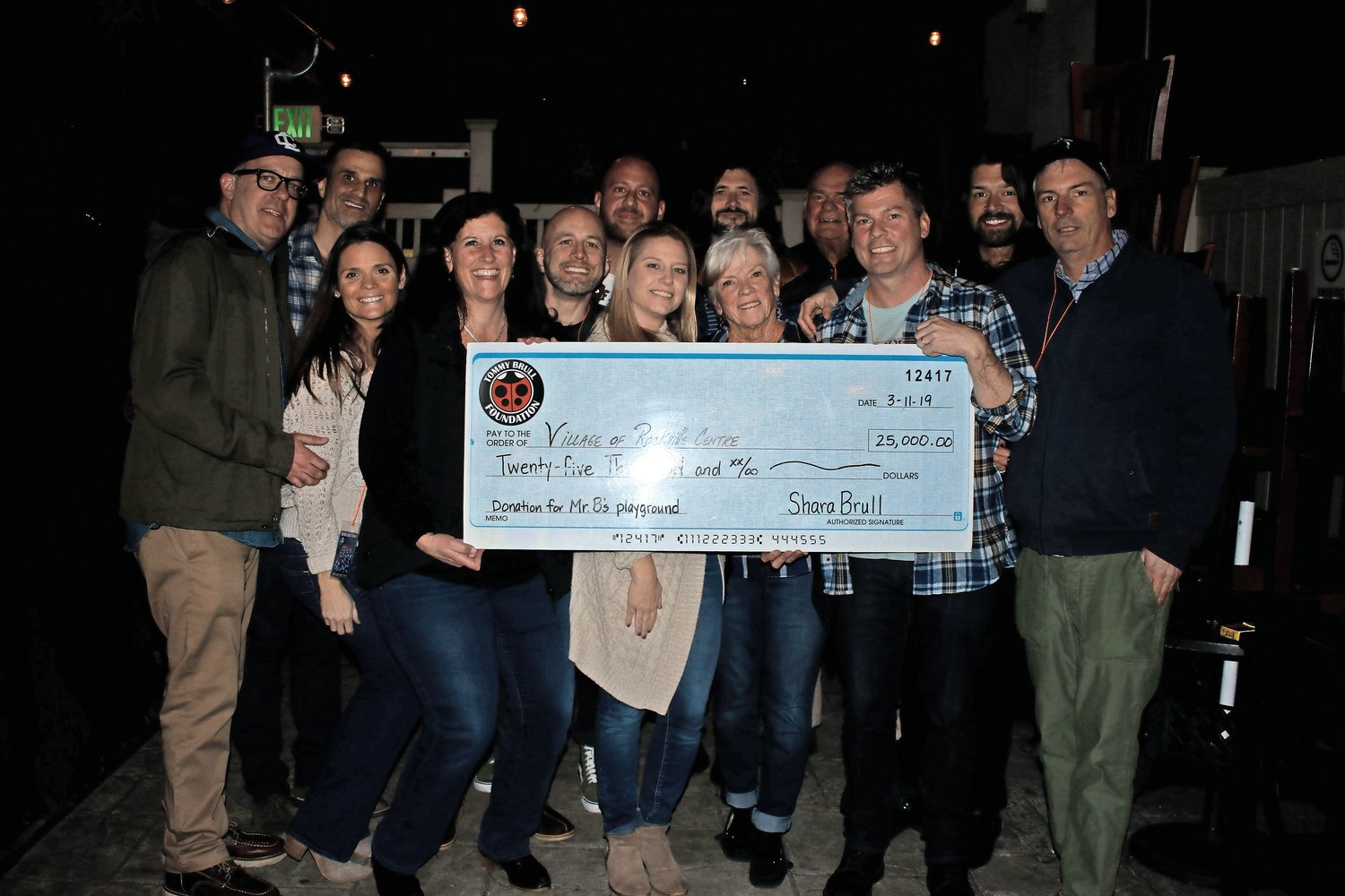 Members of Taking Back Sunday and the Tommy Brull Foundation held a check for $25,000 to be donated to Mr. B's Playground.